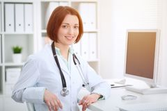 年轻深色的女性医生坐在桌上和与计算机一起使用在医院办公室 免版税库存照片