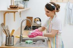 年轻深色的妇女在厨房洗着杯子和盘子 免版税库存照片