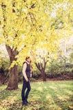 年轻深色的妇女在山毛榉树下在秋天,秀丽filt 免版税库存图片