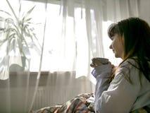 年轻深色的妇女饮用的咖啡,当坐在床上,反对窗口时 库存照片