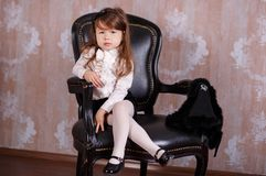 年轻深色移动式摄影车夫人女孩时髦穿戴象在摆在的白色正式衬衣黑色裙子的一个上司在演播室坐黑l 免版税库存照片