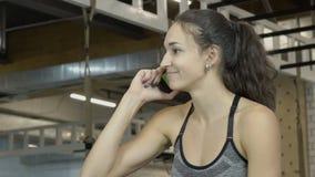 年轻深色谈话在体育俱乐部的电话 股票录像