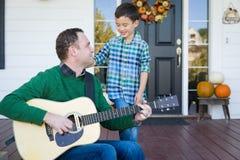 年轻混合的族种中国和白种人儿子唱歌歌曲和Pla 库存照片