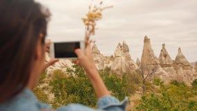 年轻混合的族种旅游女孩为美丽的山岩石照相使用手机在卡帕多细亚,土耳其 慢动作的4K 股票录像