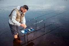 年轻渔夫在水中赤足站立 他倾斜到有人为诱饵的被打开的塑料盒 那里二 库存图片