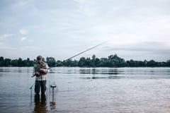年轻渔夫是在水和藏品钓鱼竿的常设barefeet 他看它 人与匙子和诱饵一起使用 图库摄影