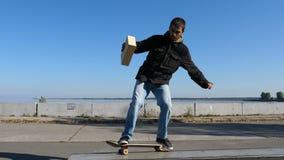 年轻溜冰者在沿壁架的一个滑板在手中滑与箱子 股票视频