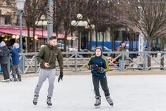年轻滑冰在一个公开滑冰的溜冰场的人和男孩户外 库存图片