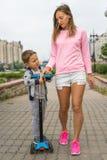 年轻滑行车的走在城市的母亲和儿子 拿着她的她的胳膊的妈妈儿子 他们是愉快的 高兴 春天 自行车、拉货车的马和驴仍然是控制的交通工具在古雅小的Mompos,人们有减速的生活 库存照片
