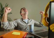 年轻满意和确信的商人激发打手势在胜利作为在家工作有便携式计算机的优胜者办公室  免版税库存照片