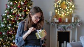 年轻激动的妇女藏品礼物,震动设法的箱子猜测什么里面,在圣诞树背景在装饰的 影视素材