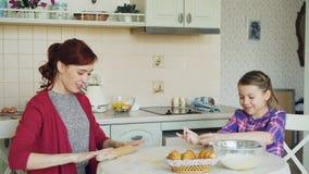 年轻烹调一起谈话的母亲和逗人喜爱的女儿在厨房里周末 小女孩拍的手用面粉 股票录像