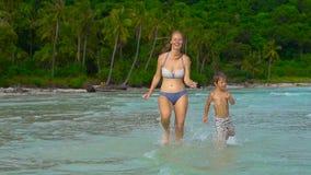 年轻爱恋的使用在海滩的母亲和她的小儿子 影视素材