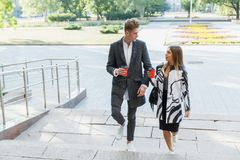 年轻爱恋的夫妇在城市附近走用咖啡 免版税库存照片