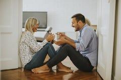 年轻爱恋的夫妇坐与数字式片剂的地板 免版税库存图片