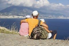 年轻父亲、女儿和儿子有背包的坐海滩反对海的背景 家庭旅行概念 免版税库存照片
