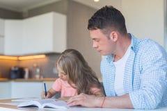 年轻父亲和一个小女儿在家 免版税库存图片
