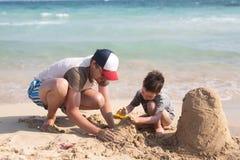 年轻父亲和他小的儿子大厦沙子城堡在海滩 免版税库存照片