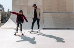 年轻父亲和他的儿子乘驾滑板在有幻灯片的一个冰鞋公园外部在好日子 免版税库存照片