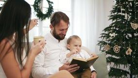 年轻父亲和他的儿子阅读书,而母亲喝茶,听他们 家庭读书圣诞节故事 影视素材