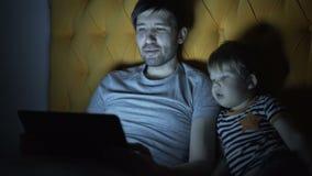 年轻父亲和他的小儿子观看的动画片电影使用便携式计算机,当在床上时在家平衡 影视素材