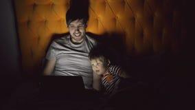 年轻父亲和他的小儿子观看的动画片电影使用片剂计算机和谈话,当在床上时在平衡 股票视频