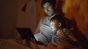 年轻父亲和他的小儿子观看的动画片电影使用片剂计算机,当在床上时在家平衡 股票录像