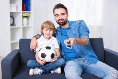 年轻父亲和儿子坐沙发和观看的橄榄球 免版税图库摄影
