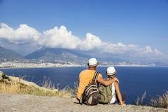 年轻父亲和儿子有背包的坐海滩反对海的背景 家庭旅行概念 库存照片