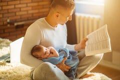 年轻父亲和阅读书对小婴孩 库存照片