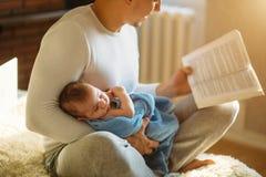 年轻父亲和阅读书对小婴孩 库存图片