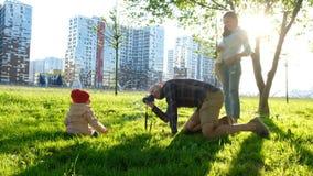 年轻父亲拍一个年轻女儿的照片在公园在日落 愉快的家庭为一个孩子照相本质上 库存照片