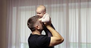 年轻父亲拿着他的胳膊和戏剧的一个小女儿与她 影视素材