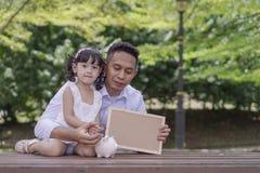 年轻父亲教他的女儿到攒钱入更好的未来的存钱罐 免版税库存照片