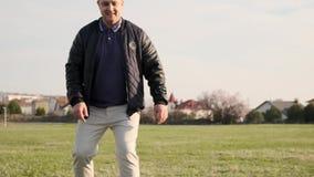 年轻父亲踢球,当踢与他的儿子和奔跑的足球在戏剧领域慢动作下时 股票录像