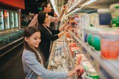 年轻父母和女儿在杂货店 他们站立在牛奶店架子和选择 女孩接触瓶子和看下来 库存图片