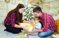 年轻父母和小孩女儿开头礼物盒在圣诞树附近在家 免版税库存图片
