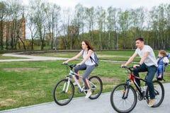 年轻父母在城市公园骑有一个小女儿的一辆自行车 库存照片