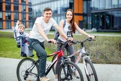 年轻父母在城市街道骑有一个小女儿的一辆自行车 免版税库存图片