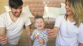 年轻父母在家庆祝他们的儿子生日灼烧的闪烁发光物和微笑 免版税库存照片