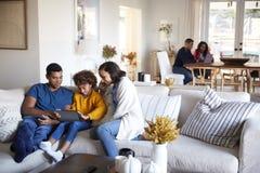 年轻父母坐有他们的使用片剂计算机的女儿的沙发在开放学制客厅,坐在桌上的祖父母 库存图片