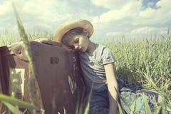 年轻牛仔放松在他重的手提箱在草甸 库存图片
