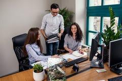 年轻牢固的经理带来与工作任务的文件夹他的雇员的 创造性的人民或广告业概念 免版税库存照片