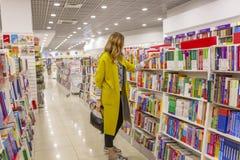 年轻现代妇女在一个大书店 免版税库存图片
