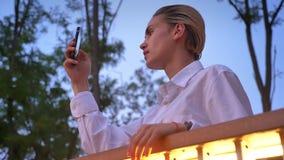 年轻现代妇女在桥梁站立,观看在她的智能手机然后拍照片,通信概念,放松 影视素材