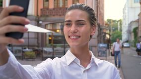 年轻现代妇女在街道上在智能手机站立并且做selfie,微笑,通信概念,都市概念 影视素材