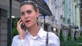 年轻现代妇女在街道上在智能手机,通信概念,都市概念站立与并且谈话 股票录像