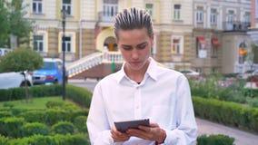 年轻现代妇女在街道上在片剂站立并且轻拍,搜寻地点,通信概念,都市 影视素材