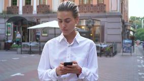 年轻现代妇女在街道上站立并且等待某人,键入在智能手机的消息,通信概念 股票录像