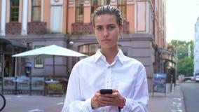 年轻现代妇女在街道上站立并且观看在照相机,键入在智能手机的消息,通信概念 股票视频